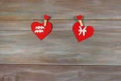 Aquário e peixes sinais do zodíaco e do coração Backgro de madeira imagem de stock