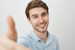 Aquí, déjeme le prestan mano Retrato del hombre caucásico amistoso encantador que tira de la mano hacia cámara como si intente as foto de archivo
