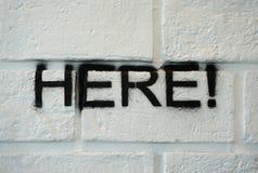 Aquí redactando en la pared de ladrillo blanca Fotografía de archivo