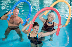 Aqua aerobics with seniors. Portrait of smiling people doing aqua fitness together in a swimming pool. Group of senior women and mature men with swim noodles Stock Photography