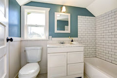 Aqua bathroom with white tile wall trim. Stock Image