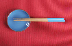 Aqua blue chopsticks and bowl on red place mat table setting. Stock Photo