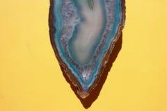 Aqua Blue Crystal Agate Stone no fundo amarelo brilhante imagens de stock royalty free