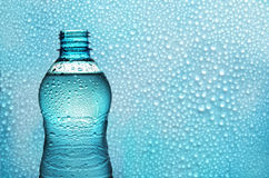 Aqua bottle on background with drops. Bottle of fresh water backlighting on background with water droplets Stock Photo