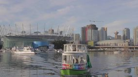 Aqua bus approaching - background BC place and downtown Vancouver. VANCOUVER,CANADA - CIRCA December 2014 :Aqua bus approaching - background BC place and stock footage