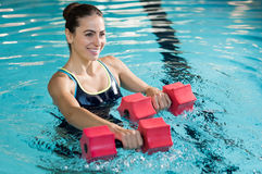 Aqua fitness. Fit woman working out with foam dumbbell in swimming pool at leisure center. Woman engaged in doing aqua aerobics in water. Young beautiful woman Royalty Free Stock Images
