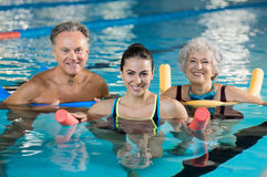 Aqua gym class. Happy mature men and old women doing aqua aerobics with foam rollers in swimming pool. Senior couple smiling with swim noodles doing aqua fitness Royalty Free Stock Photo