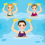 Aqua Gym Exercises. Small group of women making aqua gym exercises with dumbbells at swimming pool Stock Photo