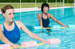 Aqua gym fitness exercise. Two young girl doing aqua gym exercise with water dumbbell in a swimming pool Royalty Free Stock Image