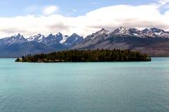 Aqua Lake ed isola ombreggiate dalle montagne feroci di Snowy fotografia stock libera da diritti