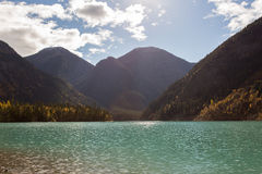 Aqua Lake Under Giant Mountains in Sun. Incredible aqua lake surrounded by mountains covered in green and gold trees during fall Stock Photo