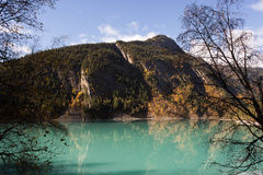 Aqua Lake Under Giant Mountains in Sun. Incredible aqua lake surrounded by mountains covered in green and gold trees during fall Royalty Free Stock Image