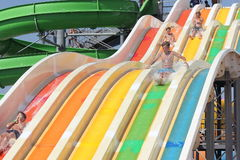 Aqua park on the beach. Fun skating children on waterslide. entertainment Royalty Free Stock Images
