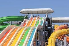 Aqua park on the beach. Fun skating children on waterslide. entertainment Stock Image