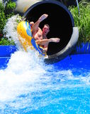 Aqua park fun - man enjoying a water tube ride Stock Photography
