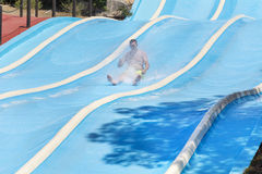 Aqua park fun -Young man riding down a water slide in water park Marineland. BARCELONA,SPAIN - JUNE 26, 2016: Marineland is a dolphinarium, marine zoo, and water Royalty Free Stock Images