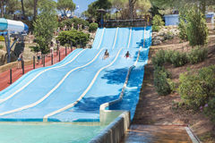 Aqua park fun -Young man riding down a water slide in water park Marineland. BARCELONA,SPAIN - JUNE 26, 2016: Marineland is a dolphinarium, marine zoo, and water Royalty Free Stock Image