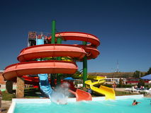 Aqua-Park Water Slide. Tri-colour water slide in aqua park, a person has just slid into the pool Royalty Free Stock Photo