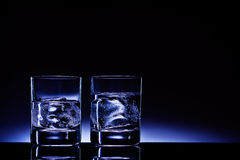 Aqua vitae!. Two glasses of vodka with ice cubes against the background of deep blue glow Royalty Free Stock Image