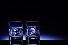 Aqua vitae!. Two glasses of vodka with ice cubes against the background of deep blue glow Stock Images