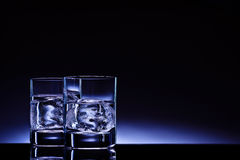 Aqua vitae!. Two glasses of vodka with ice cubes against the background of deep blue glow Royalty Free Stock Photo