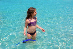 Aqua water beach and purple bikini little girl Stock Image