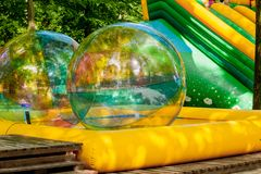 Aqua zorbing. Colorful water walking balls. Water activity for kids. Children playing together and having fun inside large. Inflatable sphere in a pool stock photo