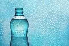 Aquaflasche auf Hintergrund mit Tropfen stockfoto
