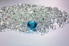 Aquamarine diamonds are placed on a pile of white diamonds