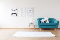 Aquamarine sofa in kid`s room. White cushions on aquamarine sofa next to cabinet and rug in kid`s room with posters stock photo