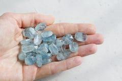 Aquamariner Stein liegt in der Hand Naturstein-Aquamarin auf einem wei?en Hintergrund Weibliche Hand kopieren Sie Platz f?r Ihren lizenzfreie stockfotografie