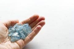Aquamariner Stein liegt in der Hand Naturstein-Aquamarin auf einem wei?en Hintergrund Weibliche Hand kopieren Sie Platz f?r Ihren stockfoto