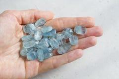 Aquamariner Stein liegt in der Hand Naturstein-Aquamarin auf einem wei?en Hintergrund Weibliche Hand kopieren Sie Platz f?r Ihren stockbilder