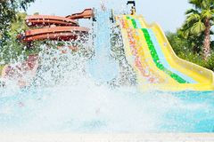 Aquapark with pool. Kid going down the hill in the aqua park. Splashes of water stock photo