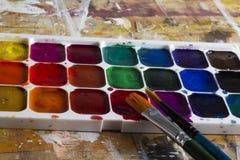 A aquarela ajustou-se e escovas em uma tabela Imagens de Stock Royalty Free