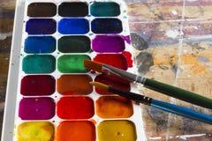 A aquarela ajustou-se e escovas em uma tabela Fotos de Stock