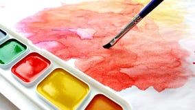 A aquarela pinta no pallete, nas escovas da arte e no desenho abstrato multicolorido da aquarela fotos de stock royalty free