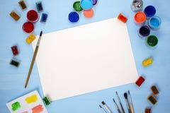 Aquarell, Acryl, Bürsten und ein Blatt Papier auf einem blauen Hintergrund Flache Lage, Draufsicht die Tabelle des Künstlers stockfoto