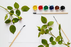 Aquarell, Bürsten, Papier und rosafarbene Blumen werden auf weißen Tabellenschreibtisch gesetzt Draufsicht, flache Lage lizenzfreie stockfotos