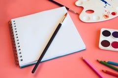 Aquarell, farbige Bleistifte und Sketchbook mit einer Leerseite auf rosa Hintergrund Stockbild