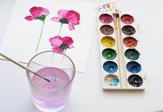 Aquarelle, Bürste und Malerei von schönen rosa Blumen auf weißem Hintergrund, künstlerischer Arbeitsplatz Lizenzfreies Stockfoto
