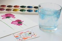 Aquarelle, Bürste und Malerei von schönen rosa Blumen auf weißem Hintergrund, künstlerischer Arbeitsplatz Stockbilder