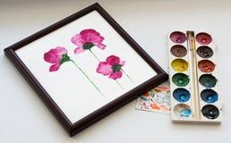 Aquarelle, Bürste und Malerei von schönen rosa Blumen im Rahmen auf weißem Hintergrund, künstlerischer Arbeitsplatz Stockbild
