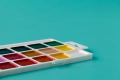 Aquarelle colors in a plastic box on a aquamarine background stock photo