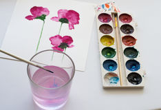 Aquarelle, künstlerische Werkzeuge und Malerei von schönen rosa Blumen auf weißem Hintergrund, künstlerischer Arbeitsplatz Lizenzfreie Stockfotos