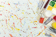 Aquarelle palette, gouache buckets and various paintbrushes. Art and craft tools top view stock image