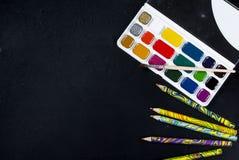 Aquarelle und Bleistifte auf einem schwarzen Hintergrund Beschneidungspfad eingeschlossen Kopieren Sie SP Lizenzfreie Stockfotos