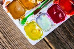 Aquarellemålarfärg-ask och borste Arkivfoton