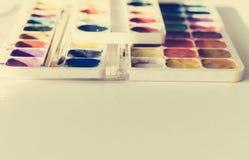 Aquarellfarbe und -bürsten gut benutzt auf weißem Holztisch mit Kopienraum für Text stockbilder