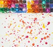 Aquarellfarben, -bürsten und -PALETTE auf dem bunten Hintergrund Stockbilder